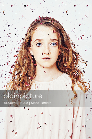 portrait of a young girl with flower petals - p1540m2211028 by Marie Tercafs