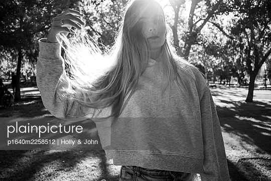 Teenage girl with blond hair in a park - p1640m2258512 by Holly & John