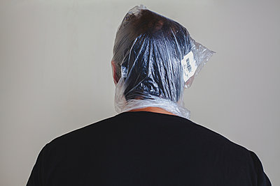 Man with a plastic bag over his head - p1165m956382 by Pierro Luca