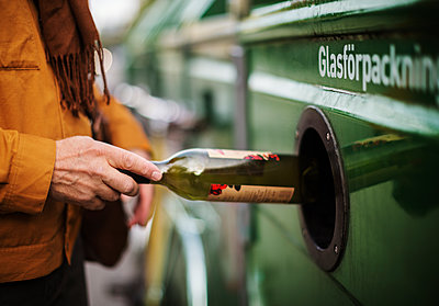 Hand putting bottle into recycling bin - p312m2091488 by Pernille Tofte