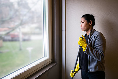 Woman holding mop and looking through window - p312m2262733 by Jens Lindström