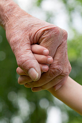 Old and young person holding hands - p8961331 by Theo van pelt