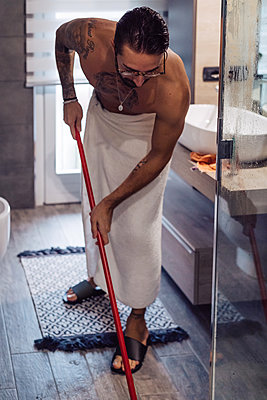Mid adult man wrapped in towel cleaning bathroom floor - p924m2097361 by Eugenio Marongiu