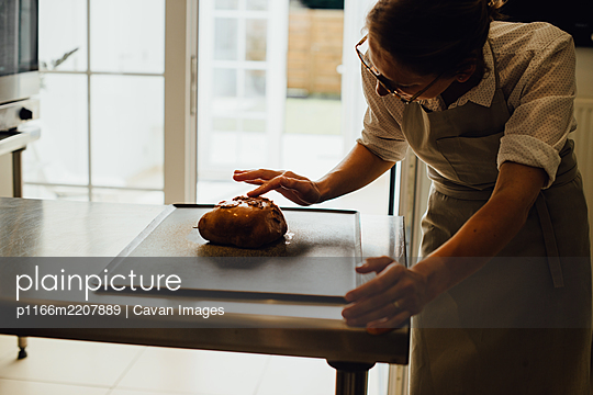 Female baker in uniform is decorating bread while working in bakery - p1166m2207889 by Cavan Images