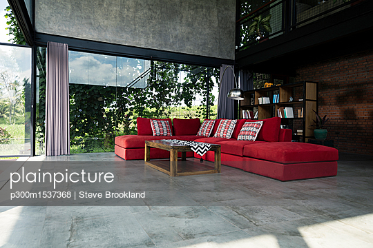 plainpicture | Photo library for authentic images - plainpicture p300m1537368 - Red couch in modern design ... - plainpicture/Westend61/Steve Brookland