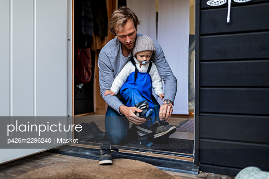 Mid adult man helping son put on shoe at doorway - p426m2296240 by Maskot