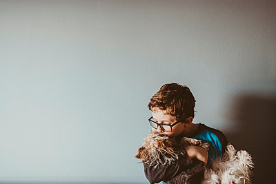 Boy kissing Yorkshire Terrier against wall at home - p1166m1416304 by Cavan Images