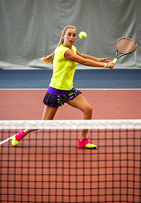 Young woman playing tennis in an indoor tennis center - p300m1059212f by Marco Govel