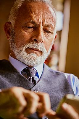 Elegant senior man using cell phone - p300m1549755 by Zeljko Dangubic
