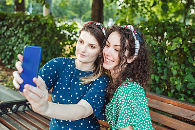 Beautiful woman taking selfie with young female friend sitting at park - p300m2226660 by Katharina und Ekaterina