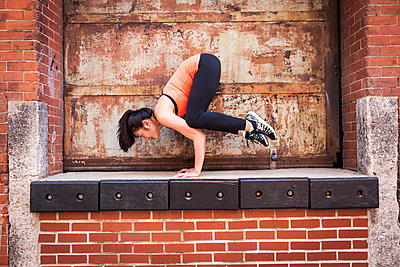 Woman Doing Exercise On Top Of Brick Wall - p343m1218171 by Lucie Wicker