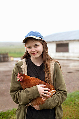 Girl carrying hen - p924m821699f by Vicky Kasala