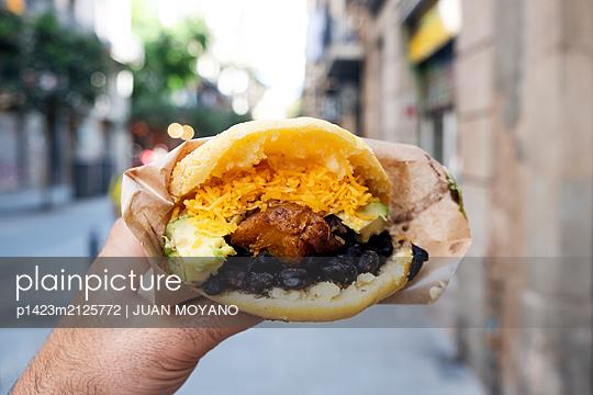 Man eating a venezuelan chicken arepa on the street in Barcelona, Spain - p1423m2125772 von JUAN MOYANO