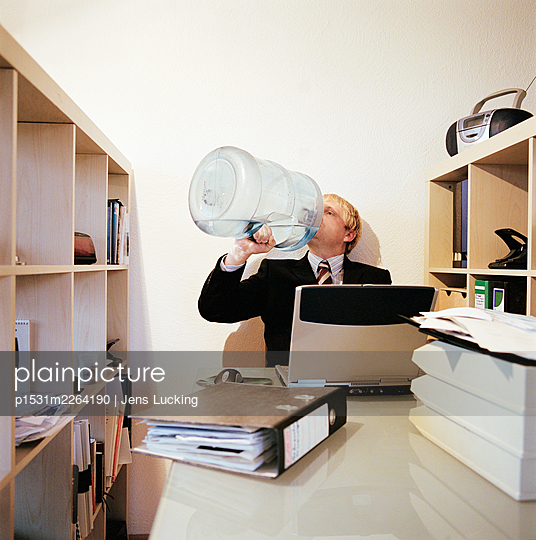 Businessman Sitting At Desk Drinking from Water Cooler Bottle - p1531m2264190 by Jens Lucking