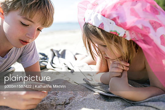 Boy and his little sister lying on the beach - p300m1587422 von Katharina Mikhrin