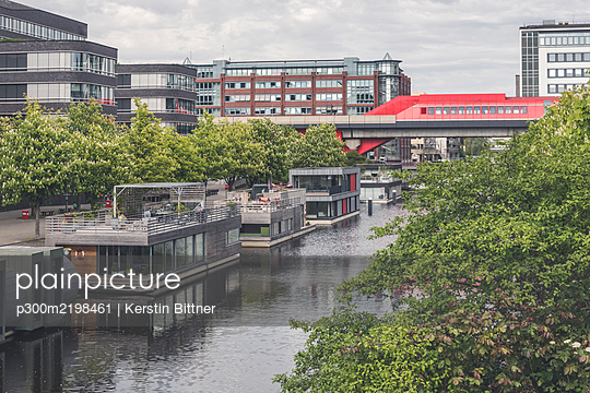 Germany, Hamburg, Houseboats along Mittelkanal with Hammerbrook Station in background - p300m2198461 by Kerstin Bittner