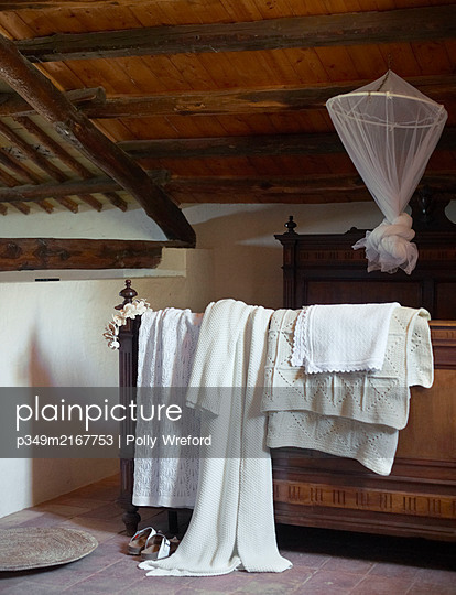 Blankets and dressing gown with mosquito net on mezzanine bed in Sicilian home - p349m2167753 by Polly Wreford