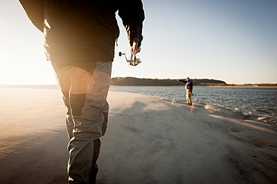 Men preparing for fishing at beach during sunset - p1166m1225989 by Cavan Images