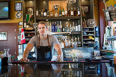 Portrait confident male bartender behind counter - p1192m1184121 by Hero Images