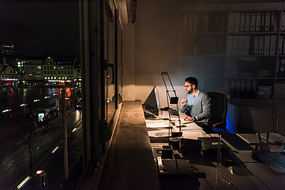 Businessman working on computer in office at night - p300m1581710 by Uwe Umstätter