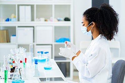 Young researcher doing scientific experiment in laboratory during pandemic - p300m2266227 by Giorgio Fochesato