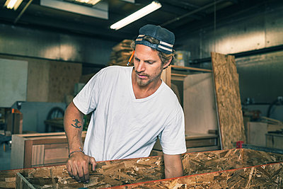 Carpenter holding wooden plank at workshop - p426m1062631f by Maskot