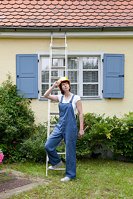 Woman cleaning the rain pipe - p4541441 by Lubitz + Dorner