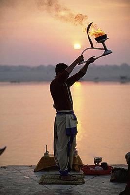 Hindu man worshipping in front of setting sun, River Ganges (Ganga), Varanasi (Benares), Uttar Pradesh state, India, Asia - p8710232 by Gavin Hellier