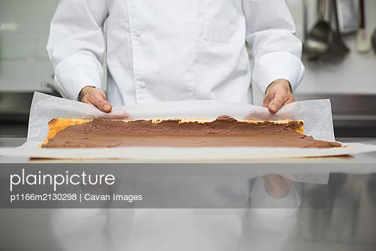 Chef preparing pastry roll with baking paper - p1166m2130298 by Cavan Images