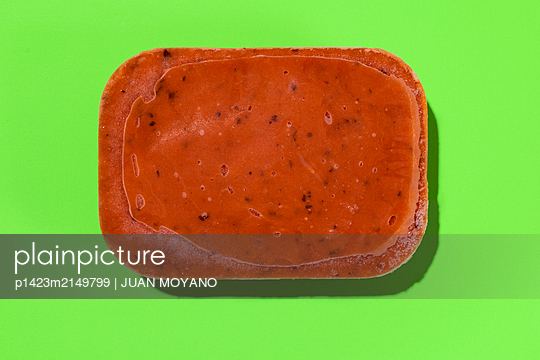 A block of frozen red soup or puree on a green background - p1423m2149799 von JUAN MOYANO