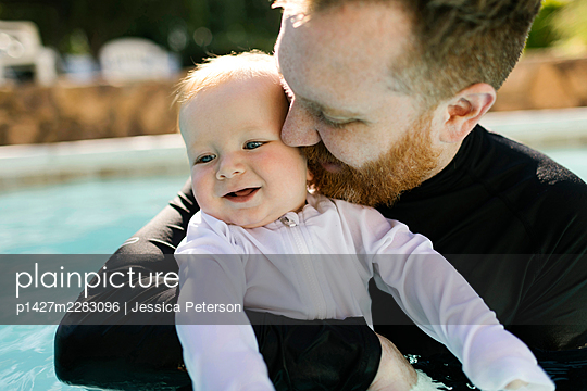 Father embracing baby son (12-17 months) in swimming pool - p1427m2283096 by Jessica Peterson