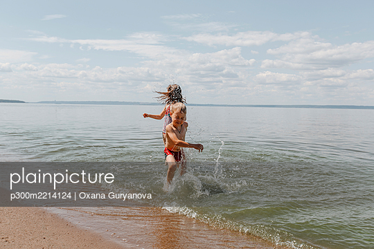 Brother and sister having fun during summer at beach - p300m2214124 by Oxana Guryanova