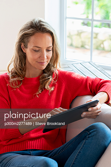 Beautiful woman using digital tablet at home - p300m2277489 by Steve Brookland