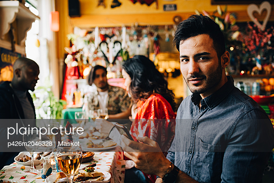 Portrait of confident young man holding smart phone while sitting with friends at table in restaurant during dinner part - p426m2046328 by Maskot