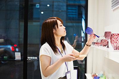 Saleswoman in a shop selling Edo Kiriko cut glass in Tokyo, Japan. - p1100m1185829 by Mint Images