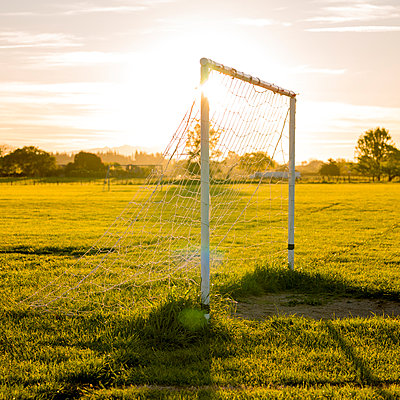 Goal posts with setting sun - p1201m1040606 by Paul Abbitt