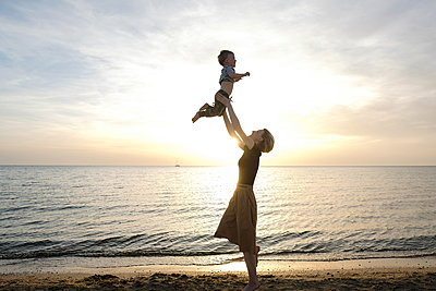 Young woman plays with her son near sea - p1363m2108783 by Valery Skurydin