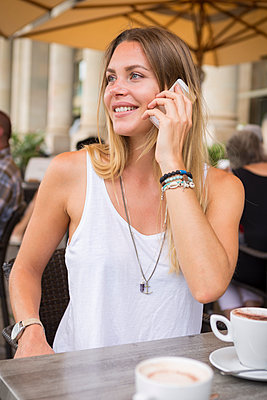 Young woman in a street cafe on cell phone looking around - p300m1505331 by JLPfeifer
