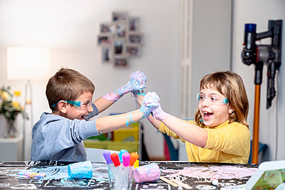 Cheerful siblings playing with slime at home - p300m2264752 by Albert Martínez