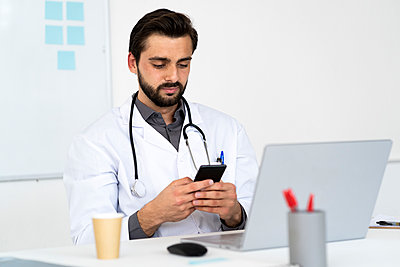 Male doctor using mobile phone while sitting at desk - p300m2275468 by Giorgio Fochesato