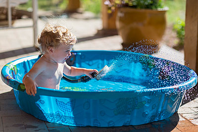 Caucasian baby playing with hose in wading pool - p555m1415343 by Marc Romanelli