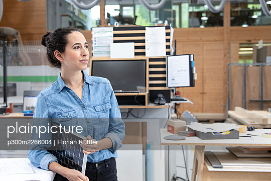 Thoughtful businesswoman holding solar panel model concept while looking away in factory - p300m2266004 by Florian Küttler
