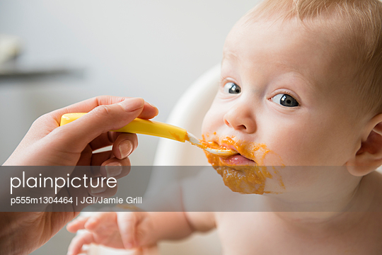 Mother feeding messy baby son with spoon in high chair - p555m1304464 by JGI/Jamie Grill