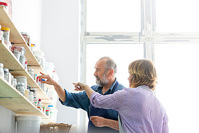 Man and woman browsing art supplies on shelves in art studio - p1023m1173721 by Lukas Olek