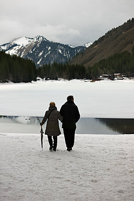 Couple walking around frozen lake - p1048m1182461 by Mark Wagner