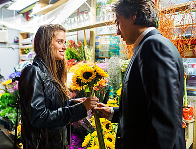 Loving boyfriend giving sunflowers to girlfriend while standing by flower shop - p1166m1203699 by Cavan Images