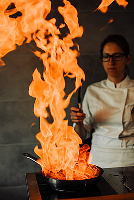 Female chef is making flambé in the restaurant kitchen - p1166m2182881 by Cavan Images