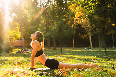 Fit young woman practicing yoga in a park - p300m2059071 von Kike Arnaiz