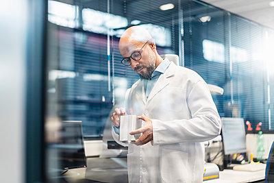Technician wearing lab coat examining workpiece - p300m2083269 by Daniel Ingold