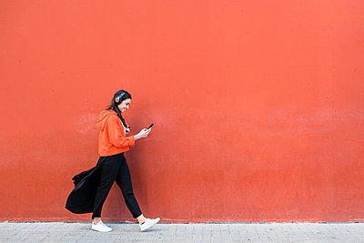 Young dancer walking and using the phone and headphones in front of a red wall - p300m2103741 von Josep Rovirosa